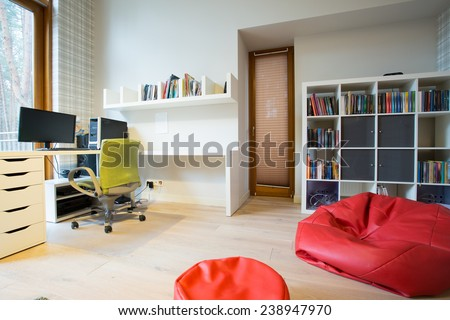 Modern spacious study room with red bag chair - stock photo