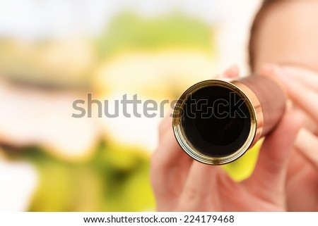 Modern spyglass in hands on bright background - stock photo