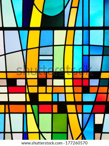 Modern stained glass window with abstract design in colors of blue, yellow, green and orange - stock photo