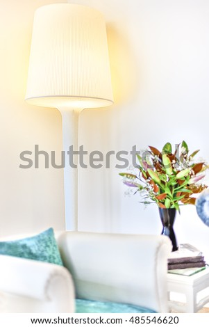 Modern stand lamp turned on near the blurred sofa and vase beside the white walls in a modern house