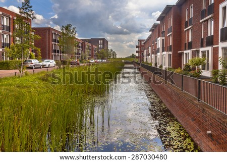Modern Street with ecological middle class family houses with eco friendly river bank in Wageningen city, Netherlands - stock photo