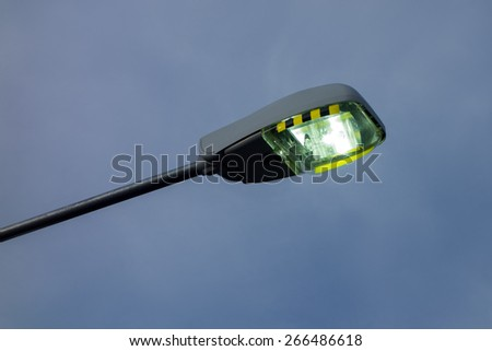 Modern streetlamp shining in the dusk sky - stock photo