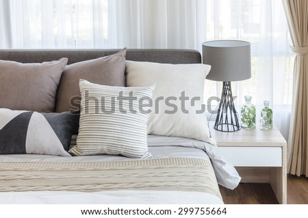 modern style bedroom with pillows on bed and modern grey lamp on side table at home - stock photo