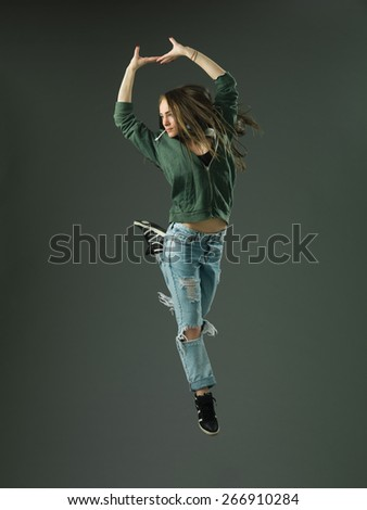modern style dancer jumping against grey studio background - stock photo