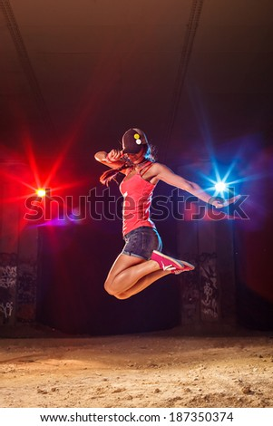 Modern style dancer jumping outdoors - stock photo