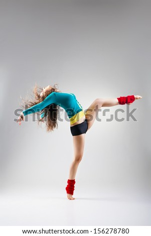 Modern style dancer posing on a studio grey background - stock photo