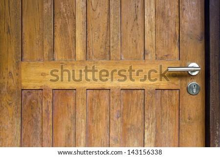 Modern  style door handle on natural wooden door - stock photo