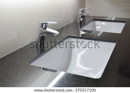 Modern style faucet with black granite counter top - stock photo