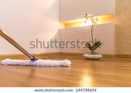 Modern style mop being used for cleaning a wooden floor - stock photo