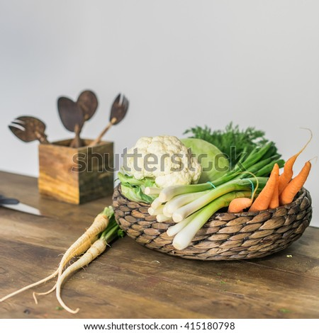 Modern stylisg kitchen tools close up knife and wooden cutting board with healthy and tasty fresh raw vegetables in wicker basket on dark brown wooden kitchen table - stock photo