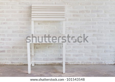 Modern stylish chair against a brick wall - stock photo