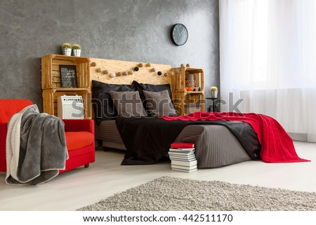 Modern stylish design of spacious bedroom. Grey walls and grey and red bed with wooden shelves on the both side