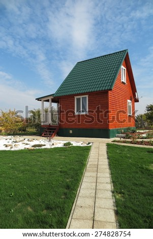 Modern summer cottage against a blue sky in the autumn garden - stock photo