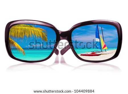 Modern sunglasses with a tropical beach scene and sailing boats reflected on the glass
