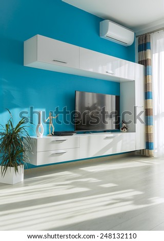 Modern sunny living room with TV - stock photo