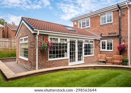 Modern Sunroom external / Modern Sunroom or conservatory extending into the garden, surrounded by a block paved patio - stock photo