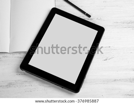 Modern tablet and notebook on white wooden background