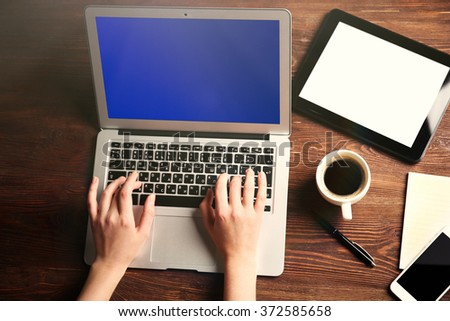 Modern tablet, mobile phone, coffee cup and female hands using laptop, on the wooden background - stock photo