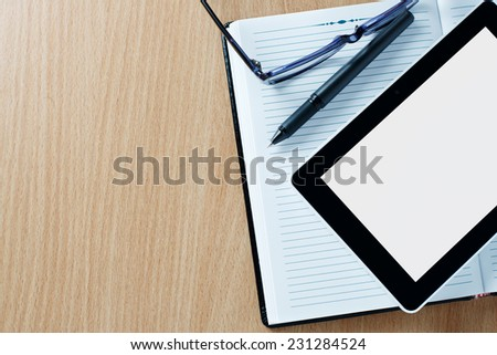Modern tablet PC displaying a white page next to eyeglasses and a pen on a classical open agenda or notebook with empty pages, on a wooden table or desk - stock photo