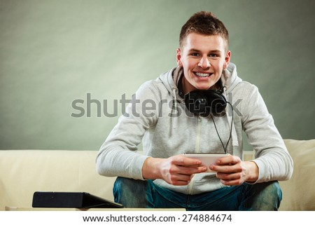 Modern technologies connection leisure concept. Young handsome man relaxing on couch with headphones smartphone and tablet at home - stock photo