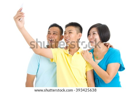 Modern technology, age and people concept. Asian boy with his parent taking selfie, using smartphone, self photographing. - stock photo