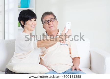 Modern technology, age and people concept. Asian senior couple selfie, using smartphone, self photographing. Family living lifestyle at home. - stock photo