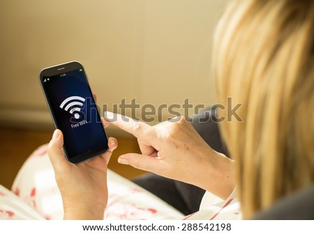modern technology and wireless communications concept:  woman with 3g generated smartphone with free wifi interface on the screen. All screen graphics made up. - stock photo