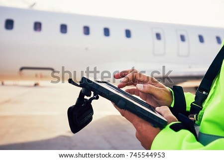 Modern technology at the airport. Member of the ground staff preparing the passenger airplane before flight.