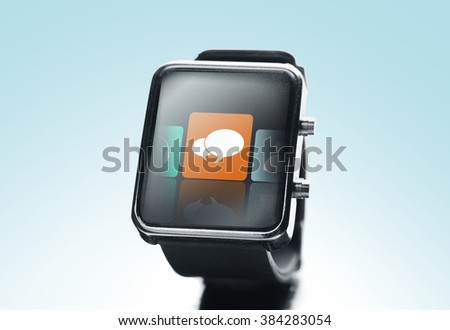 modern technology, communication, object and media concept - close up of black smart watch with text bubble icon on screen over blue background - stock photo