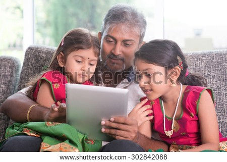 Modern technology concept. Indian family at home. Asian father and children using touch screen tablet computer, sitting on sofa, home schooling concept.