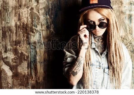 Modern teenage girl with blonde dreadlocks over grunge background. Jeans style. Modern generation. - stock photo