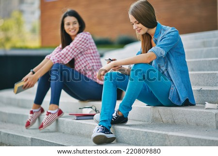 Modern teenage student reading or writing sms while sitting on stairs - stock photo