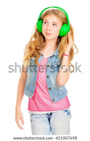 Modern teenager girl listening to music in headphones. Studio shot. Isolated over white. Copy space.  - stock photo