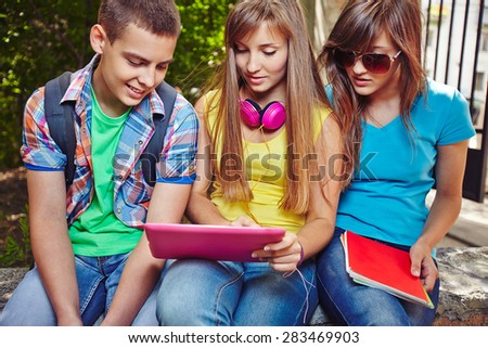 Modern teenagers with touchpad discussing homework after school