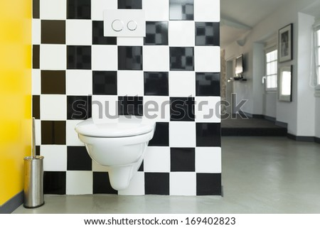 Modern toilet room with checkered black and white tiles on walls.