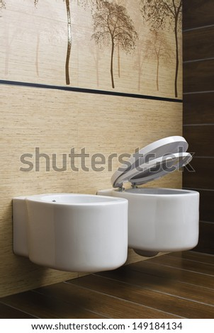 modern toilet with beige tile on wall - stock photo