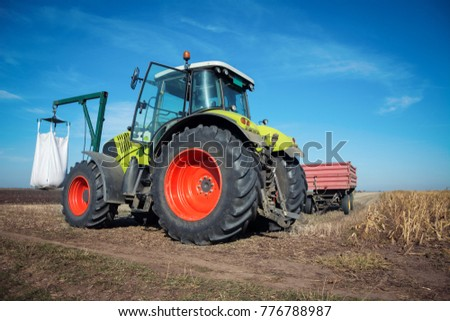 Modern tractor working in a field on a sunny day. Agricultural machinery during planting.