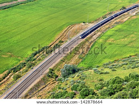 Modern train passing through green country landscape - stock photo