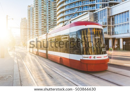 Modern tram in Toronto downtown at sunset. There is no traffic in the road, and nobody on the platform. Travel and transportation concepts.