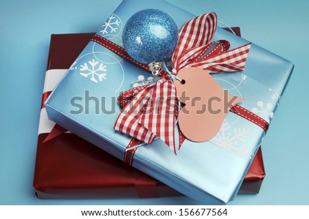 Modern trend for Christmas decor color theme of aqua blue and red gift wrapped presents, with festive berry and bauble decorations. - stock photo