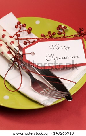 Modern trend lime green and red Merry Christmas table place setting. Vertical close up.