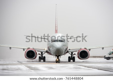 Modern twin-engine passenger airplane taxiing for take off at airport during snow blizzard