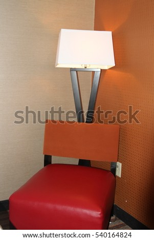 Modern two tone leather chair and stand up lamp in the corner of a room