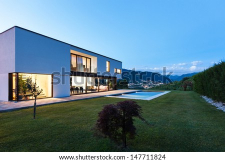 Modern villa with pool, view from garden, night scene - stock photo