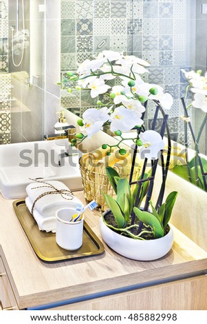Modern washroom white flower decoration on the wooden counter top, the mirror on the wall with the reflection near the towels on the  metal grill basket, the white washstand with a tap