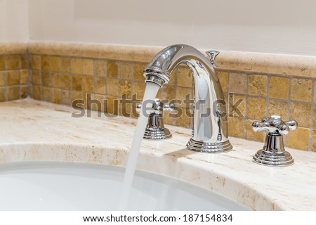 Modern water tap in the bathroom. Flowing water. - stock photo