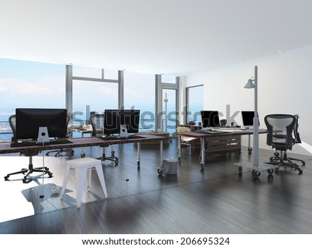 Modern waterfront office overlooking the sea with several computer workstations on movable wheeled office tables in a bright airy room with a glass view window or wall - stock photo