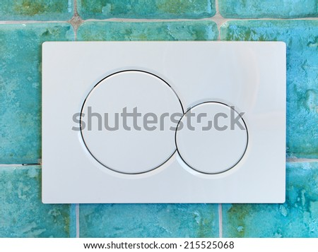 modern wc flush in a turquoise wall - stock photo