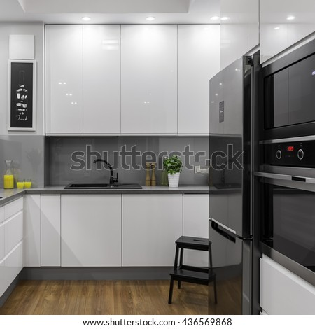 Modern white and light kitchen with steel fridge