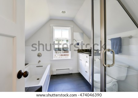 Modern white bathroom interior in the attic. The room has vaulted ceiling, view of glass shower door, bathroom vanity with black top and bathtub. Northwest, USA